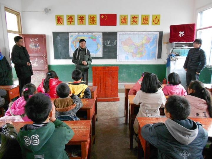 A volunteer teaches the children the location of Macao and Guiyang on the map