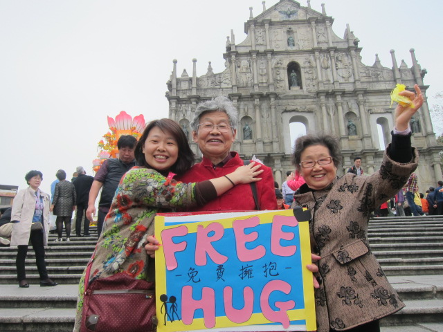 "A family of three hug under the ""Free Hug"" placard"