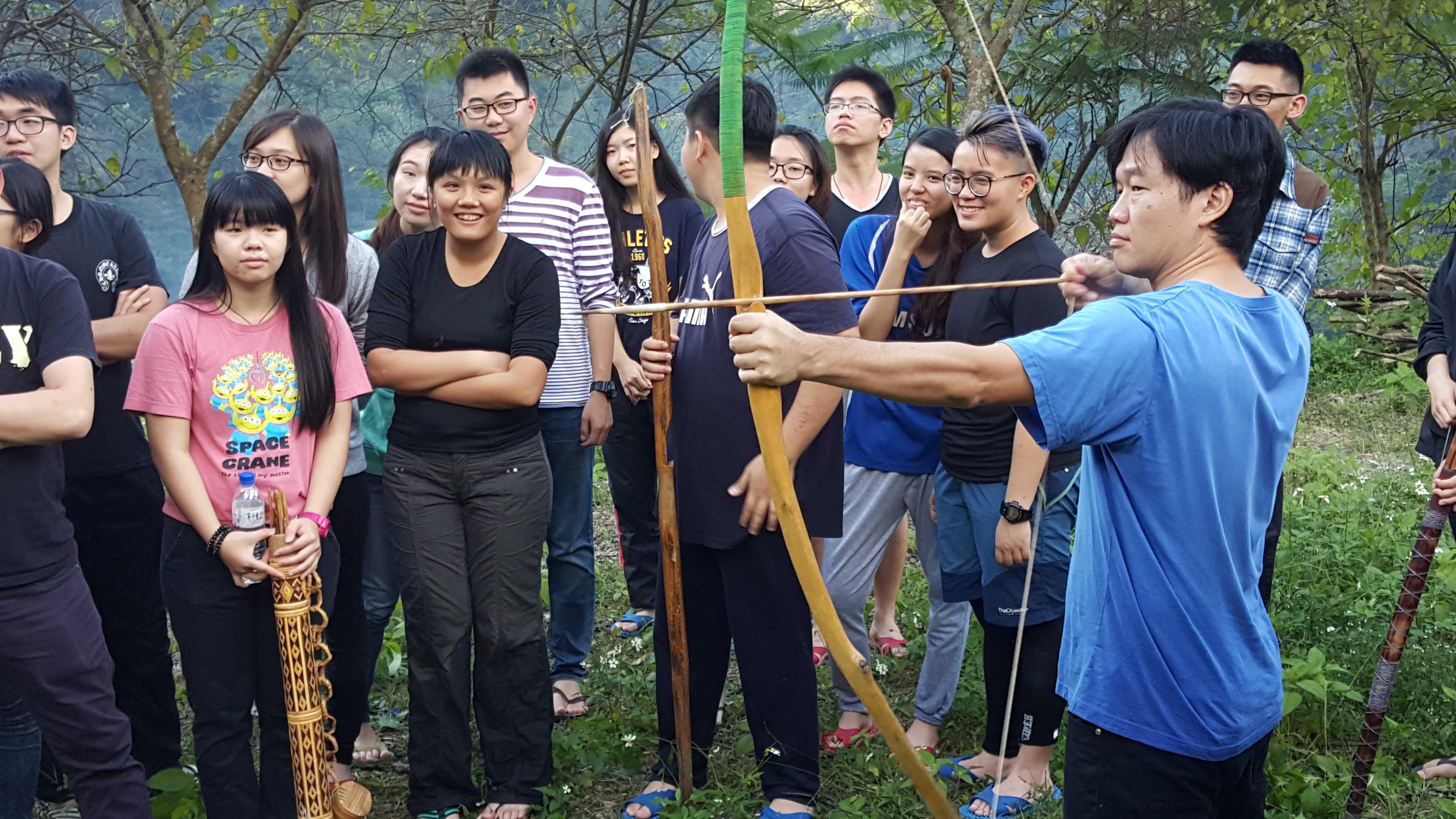師生們在原住民教導下練習射箭