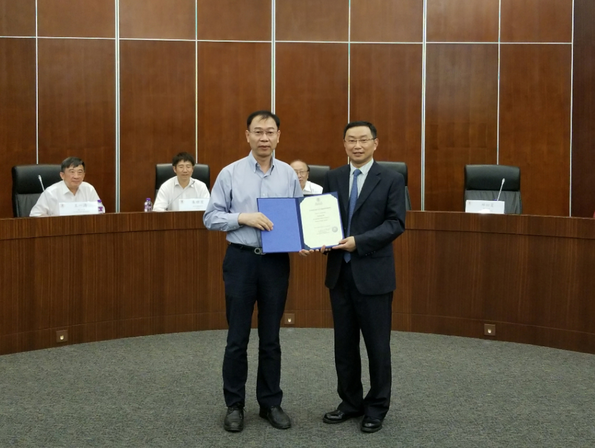 Chuxia Deng presents a certificate of appointment to He Yanzheng.