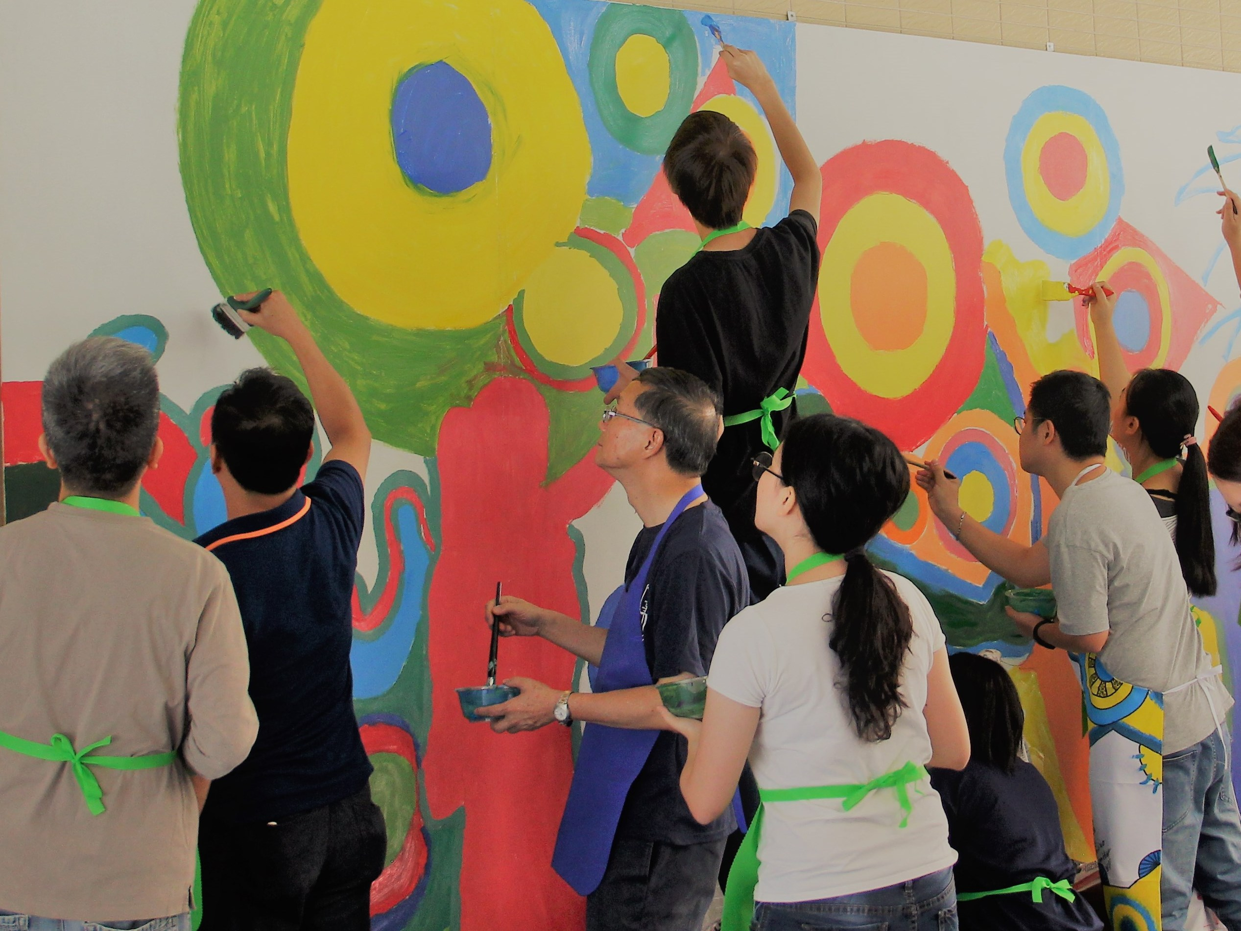 Faculty members and students paint on the wall
