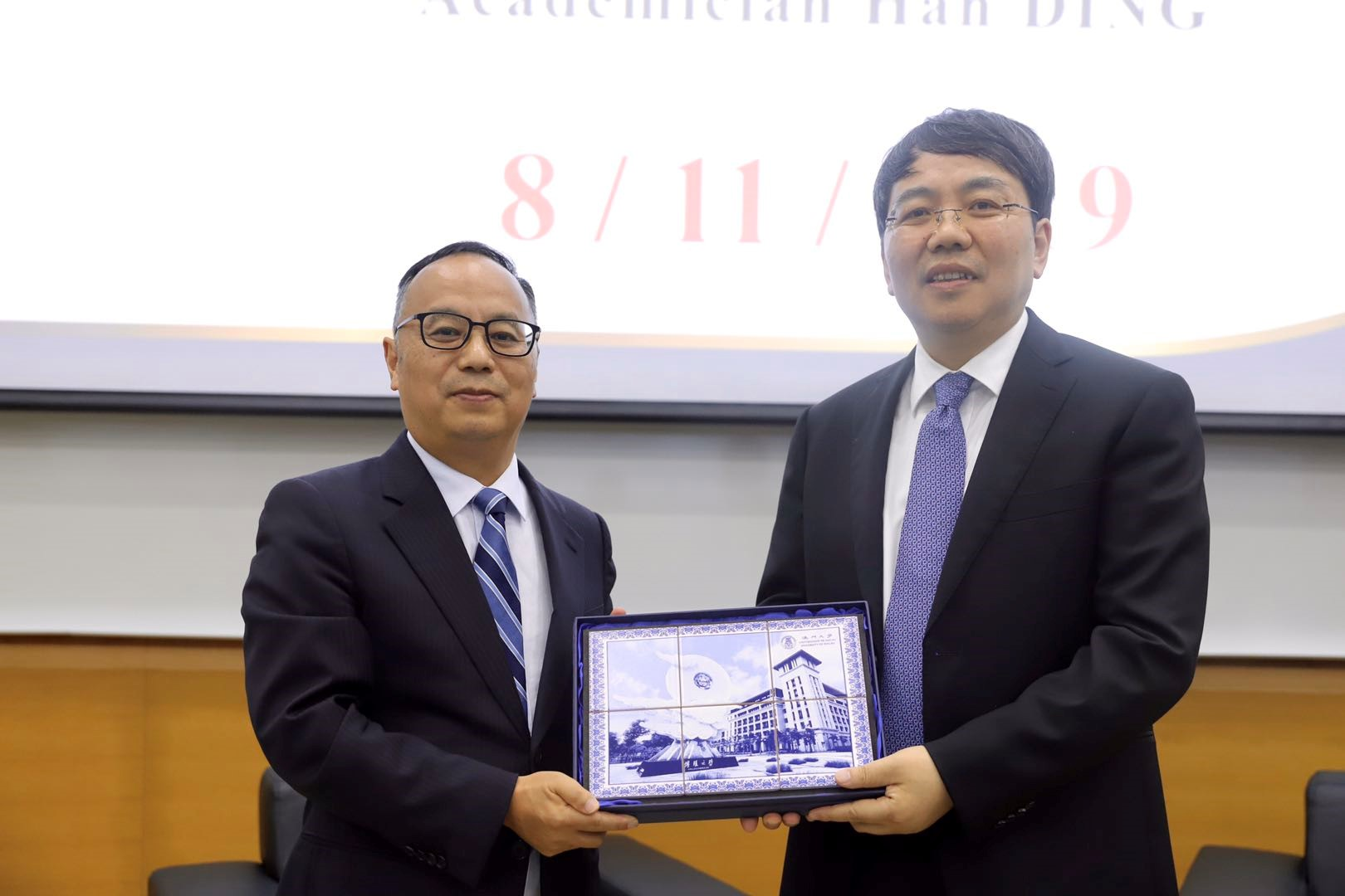 Rector Yonghua Song (left) presents a souvenir to Ding Han