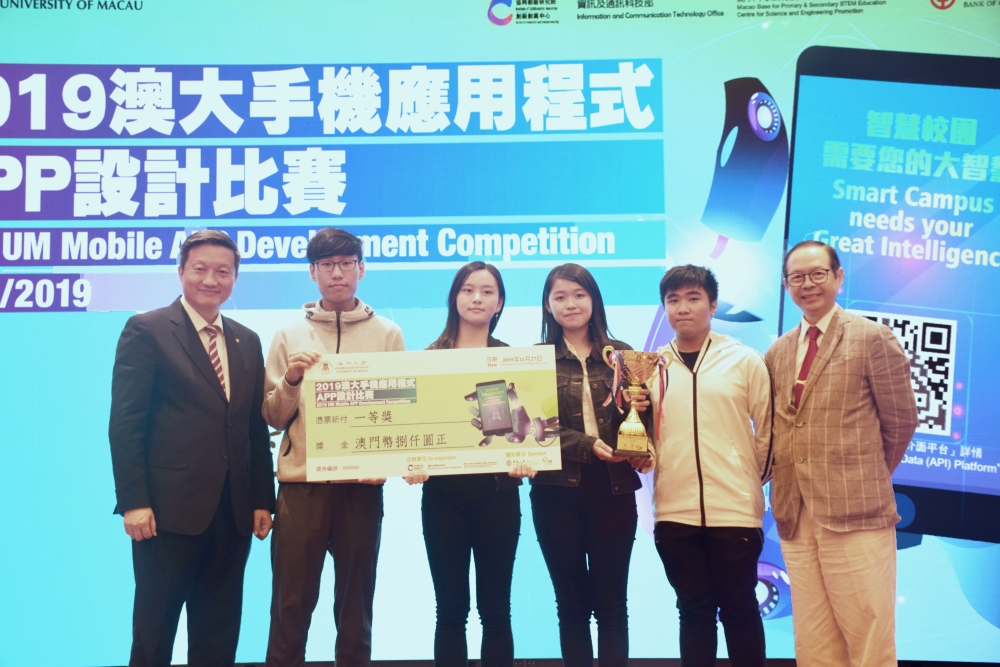 A representative of the Bank of China Macau Branch (left) and Billy So (right) present the first prize in the UM Fitness category